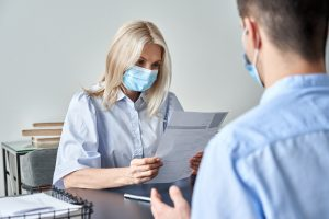 Female hr manager, employer wearing face mask reading cv at job interview.15482
